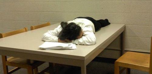 机の上で眠る女性