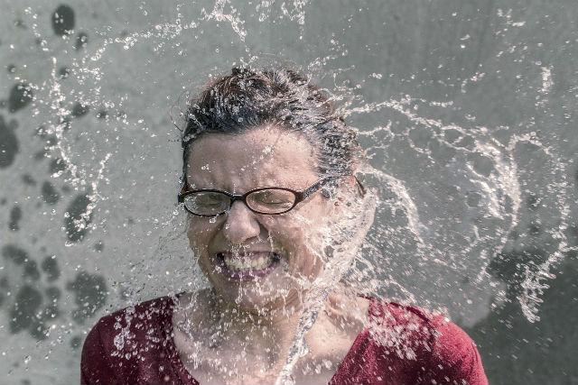 水をかぶり体温を下げている女性