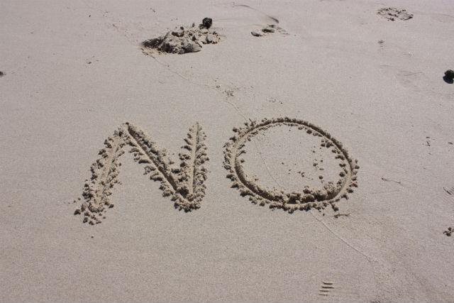 砂浜に書かれたNOの写真