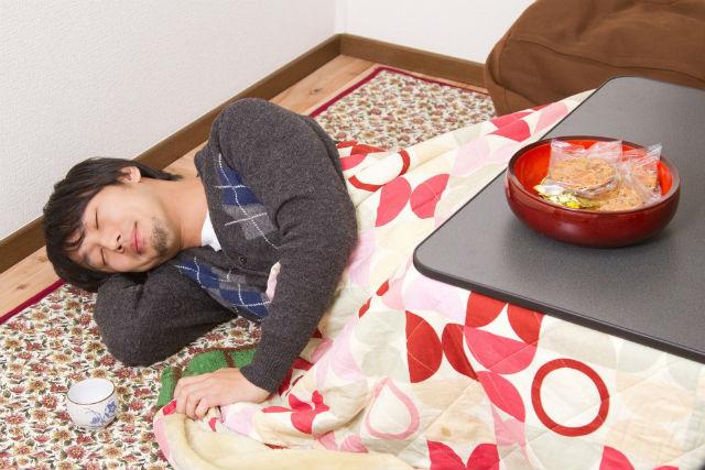 コタツで眠る男性
