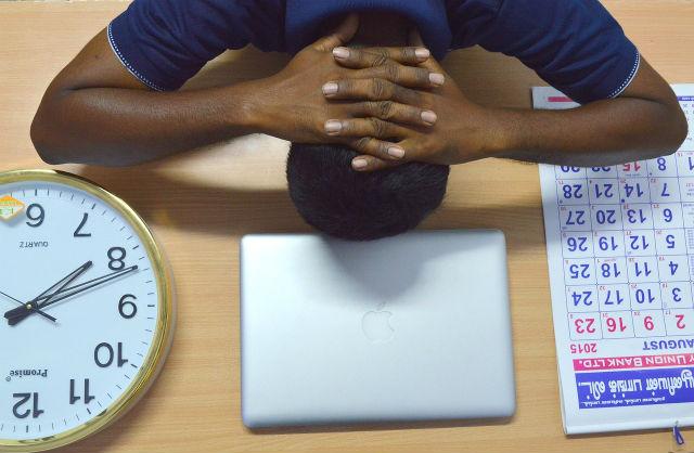 ストレスで頭をかかえる男性