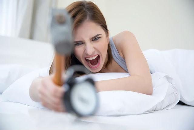 目覚まし時計を壊す女性