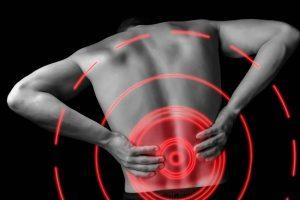 腰痛で腰を支える男性の画像
