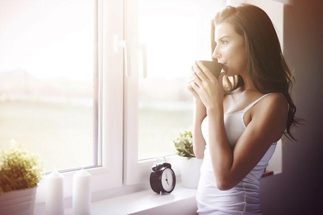 朝にコーヒーを飲む女性の画像