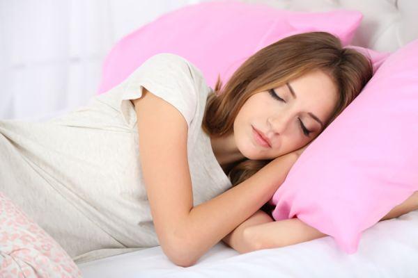 腰痛で痛みに耐えながら眠っている女性の画像
