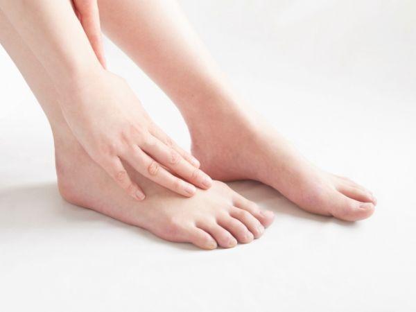 足をさすっている女性の画像