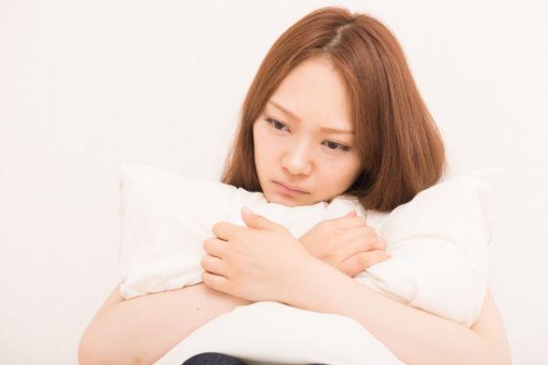 不安な様子で枕をかかえる女性の画像