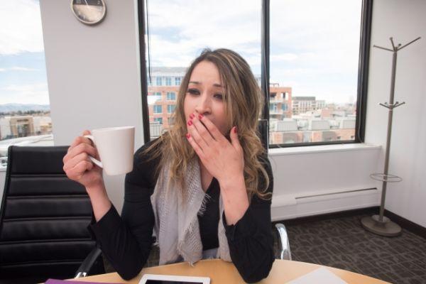 オフィスで眠気を感じている女性の画像