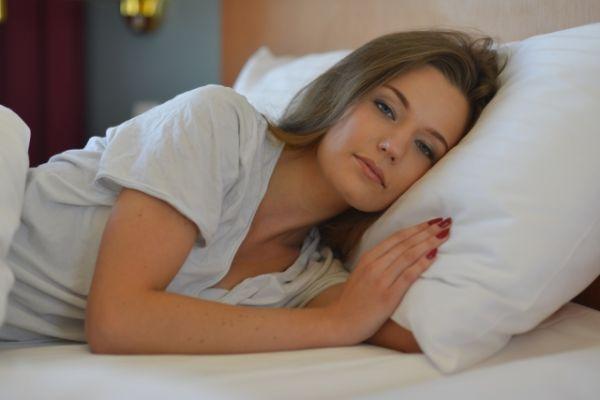 不機嫌そうな寝起きの女性の画像