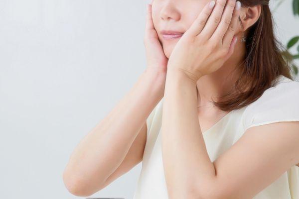 頬に手をあてている女性の画像