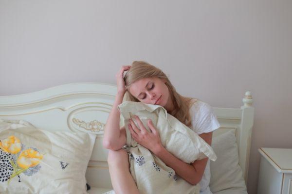 枕を持っている女性の画像