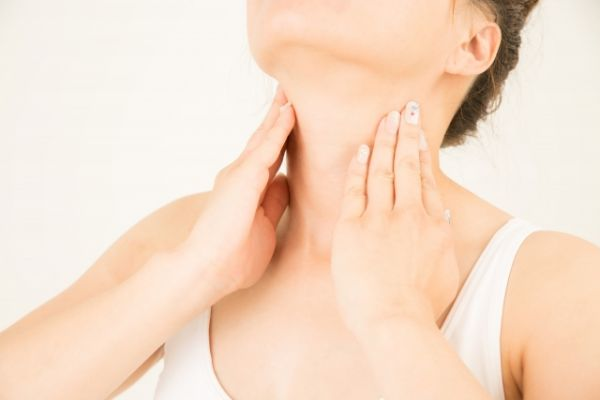 首のマッサージをしている女性の画像