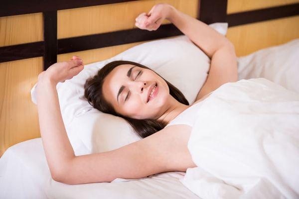 高めの枕で眠る女性の画像