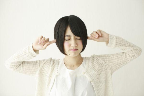 耳をふさいでいる女性の画像