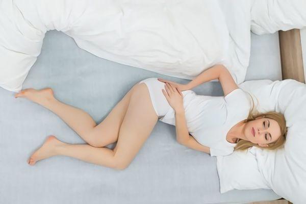 ベッドで腰を抑えている女性の画像