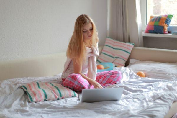 ベッドでPCを見ている女性の画像