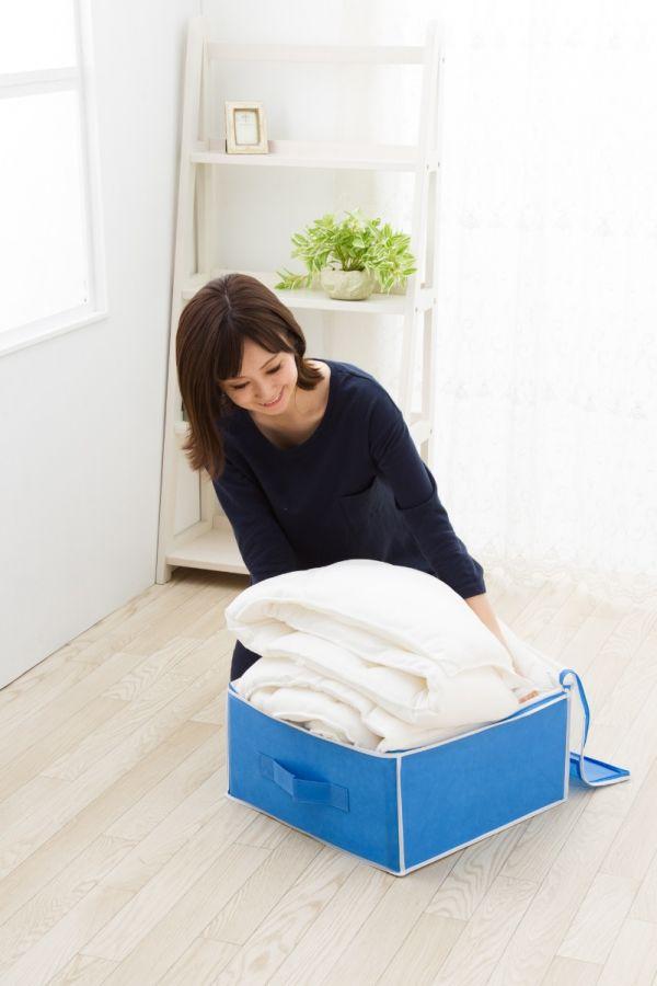 羽毛布団を通気性の良いケースに入れる女性